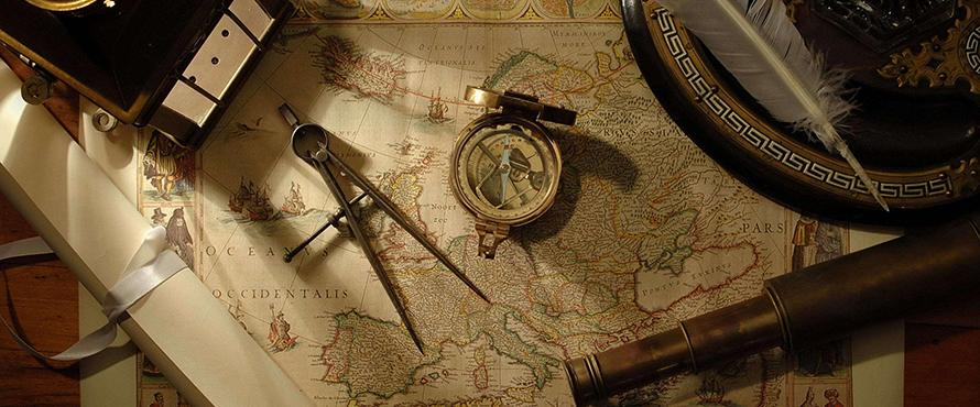 A compass, quill and other mapmaking tools lie atop an old map of the world