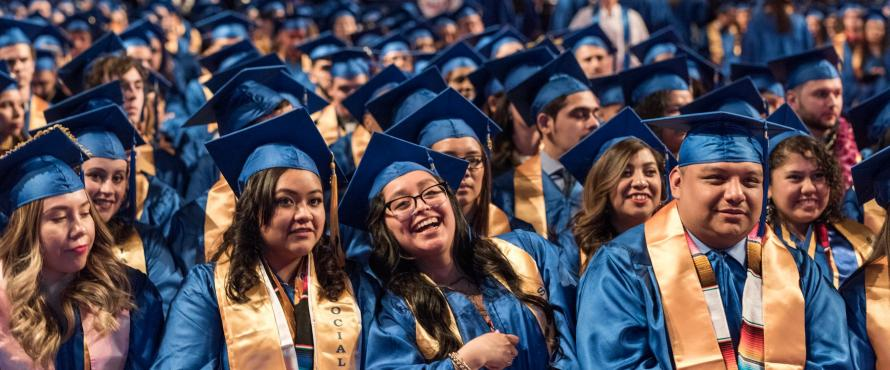 Graduates smile while wearing blue caps and gowns.