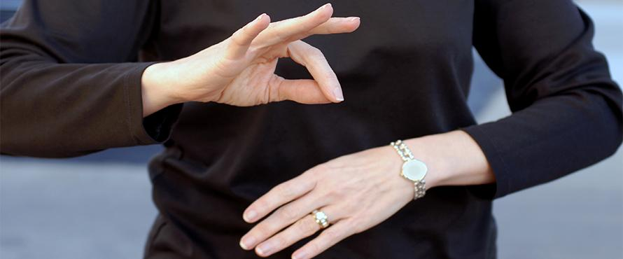 Hands are shown doing sign language in front of a body wearing a black shirt.