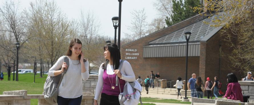 Two female students walking outdoors near the Ronald Williams Library