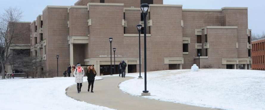 The western exterior of Bernard Brommel Hall in winter with people walking on the paths of the University Commons in the foreground