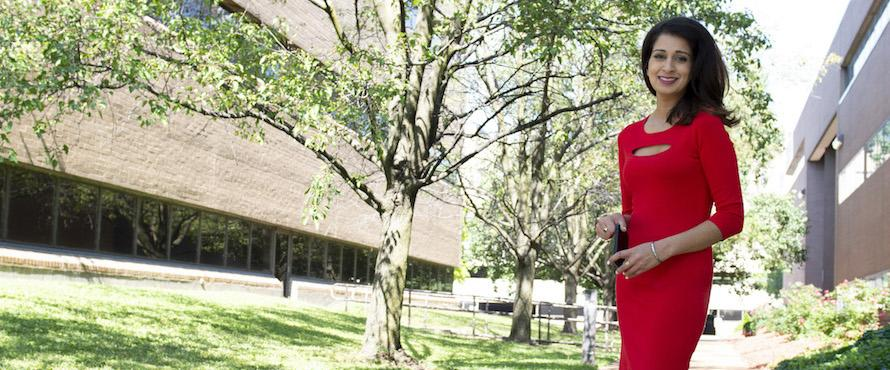 PJ Randhawa  wearing a red dress stand outdoors with trees in the background