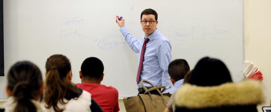 A photo of a male in a blue shirt and red tie looks at a class while standing at a white board