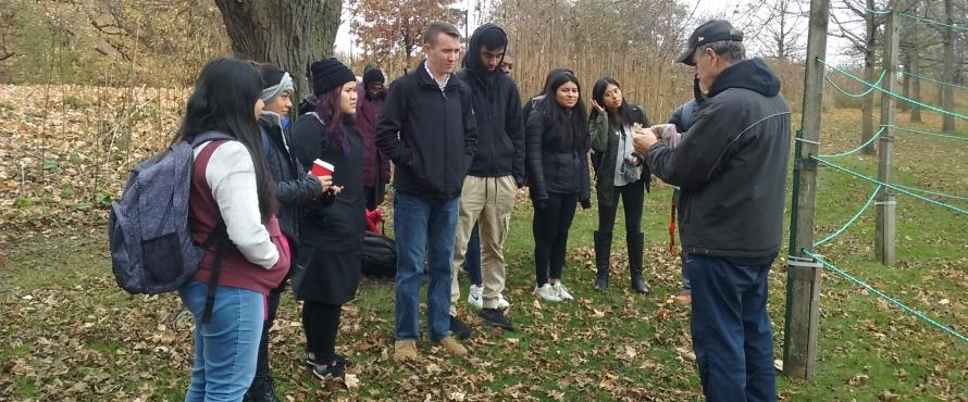 Dan Creely (right) teaches eight students while standing under a tree.