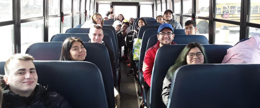 Several students smile into a camera from their seats on a bus.