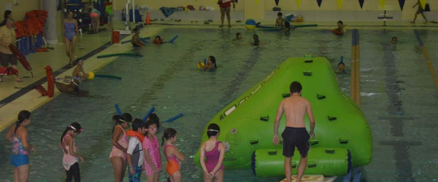 Kids play on an inflatable slide in the pool.