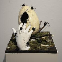 Sculpture with a hand emerging from the ground touches a large cracked egg as black spiders crawl on both