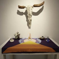 An animal skull hangs over a cloth covered altar upon which are candles and photographs