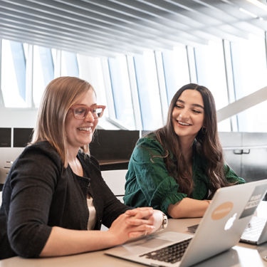 Two women smile while working together on a computer.