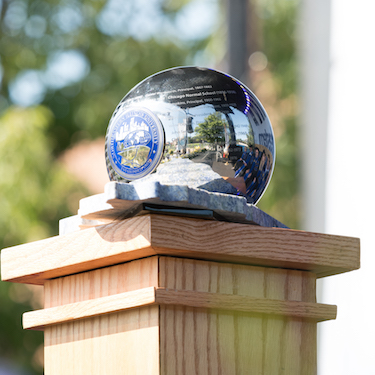 The University orb resting atop its marble base set on top of a wooden column