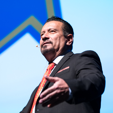 Goodwin Lecture speaker Richard P. Montañez stands on stage with a large NEIU logo in the background