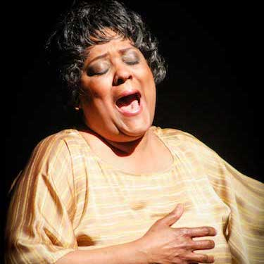 Photo of a woman with short, curly black hair wearing a gold blouse, appears to be singing.