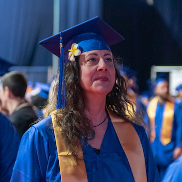 A graduate stands in her blue cap and gown.