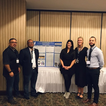 "Photo of Moises Clambas (left), Allen Ramirez, Carolyn Crost, Trace Chase and Michael Ortega pose with their student research presentation, ""The Effects of Technology on College Students' Physical Activity Levels"" at IAHPERD."