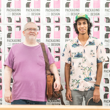 Larry O. Dean and Carlos Bernabe stand together in front of a pink, white and gray graphic design background