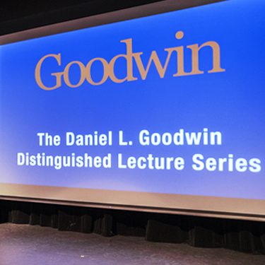 The stage of Northeastern's Auditorium with a large backdrop that reads Goodwin Distinguished Lecture Series