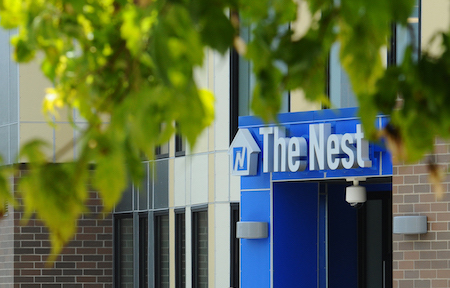The Nest logo is shown in blue and white over the main entrance to the residence hall.