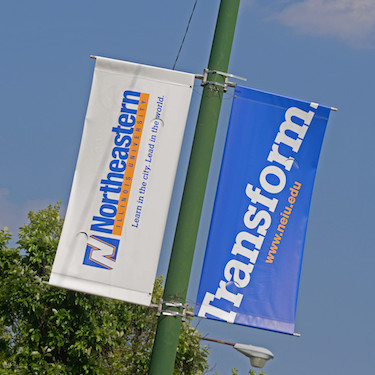 Two banners hang from street light poles; one reads Northeastern Illinois University, the other reads Transform