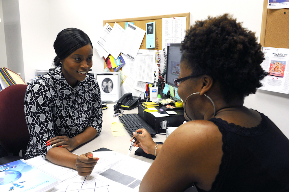 Advisor Amie Jatta (left) meets with a student in her office.
