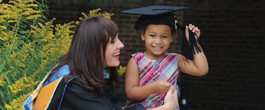 Graduate in gown with daughter wearing cap, both smiling.