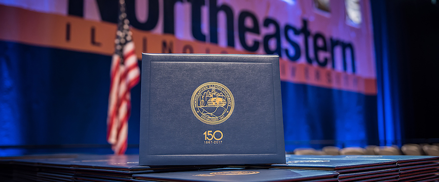 A diploma cover sits in front of the American flag and a Northeastern Illinois University banner.