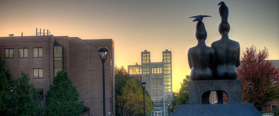 "The ""Serenity"" statue on the University Commons as seen from behind with the Library and Parking Facility in the background against a sunset sky"