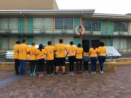 A group of Alternative Spring Break students in yellow shirts visit the site of Dr. Martin Luther King's assassination
