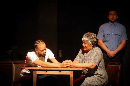 Two actors sit at a table while performing a Black Ensemble Theater play.