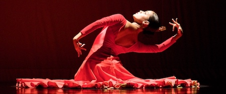 A woman dances in a red dress against a black background