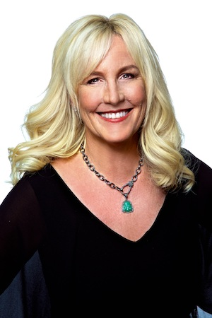 Erin Brockovich smiles into the camera in front of a white background.