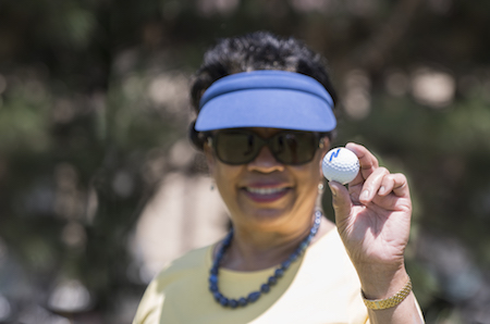 President Gloria J. Gibson holds a golf ball up to the camera.