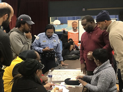 Troy Harden with David Rivers and Englewood residents at a community meeting discussing research over a map of the community