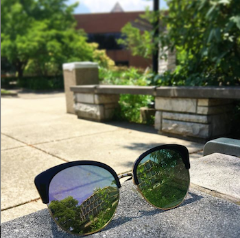 A building is reflected in a pair of sunglasses that sit on a table.