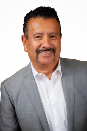 Photo of Richard P. Montañez wearing a white button-down shirt and gray suit jacket