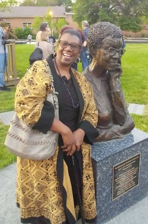 Photo of a smiling Sherry Williams in a black shirt and yellow and black patterned jacket standing next to the Gwendolyn Brooks statue in Bronzeville