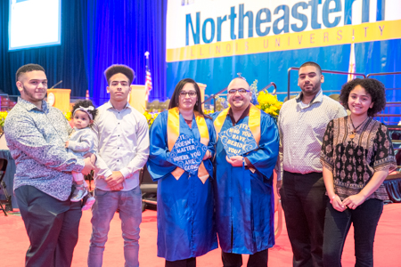 Ruby and Joel Rodriguez pose with their family in front of the Commencement stage.