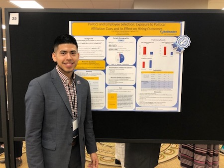 Uriel Saldivar smiles in front of his winning poster presentation.