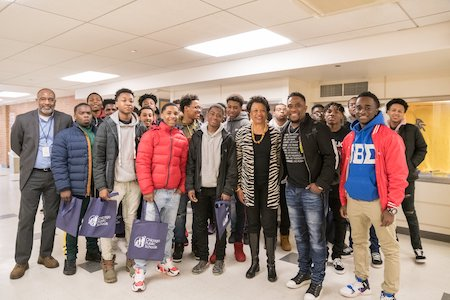 More than a dozen young men pose with President Gibson at the 6th Annual Young Men of Color Summit at Northeastern
