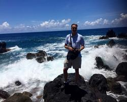 Honors Program Coordinator Jon Hageman standing on a rocky seaside