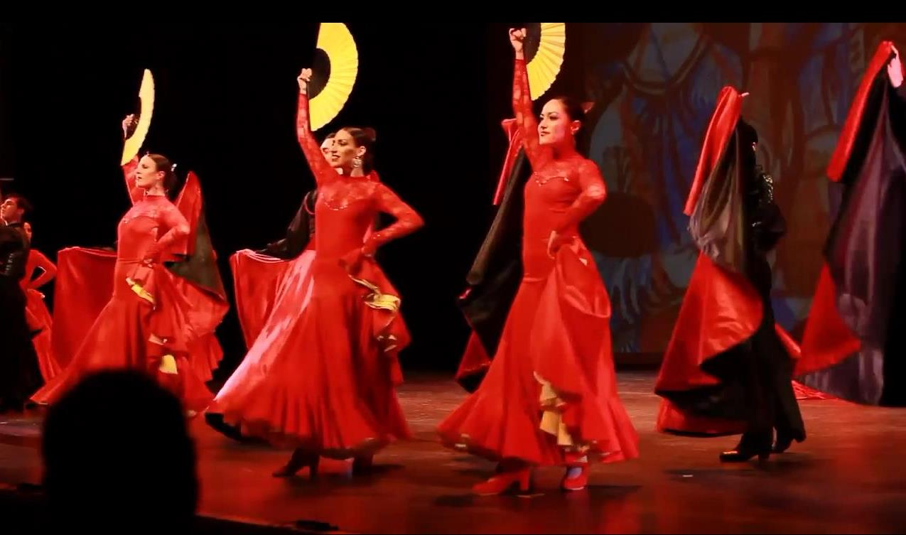 Female dancers in red dresses raise open yellow fans