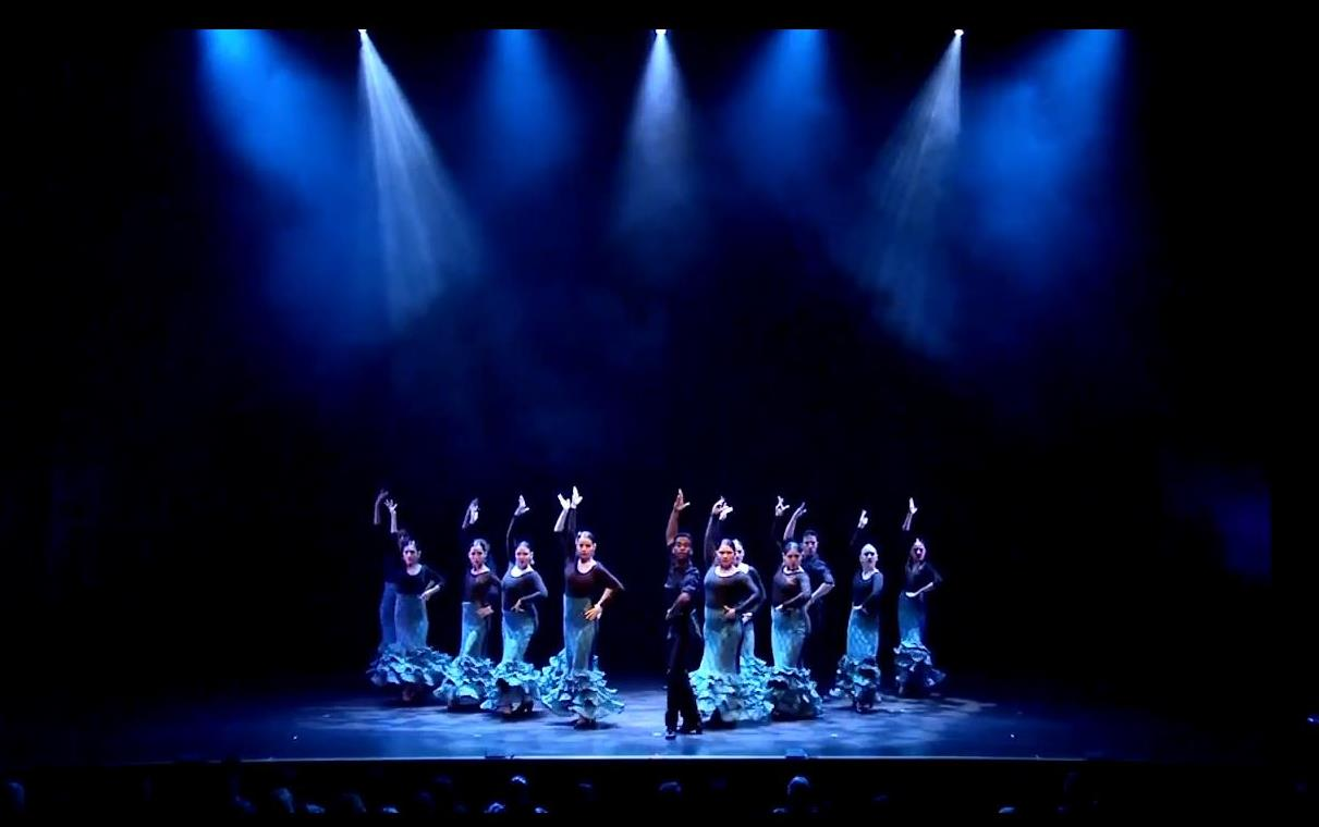 One male and 10 female dancers strike a pose on a stage lit with blue lighting