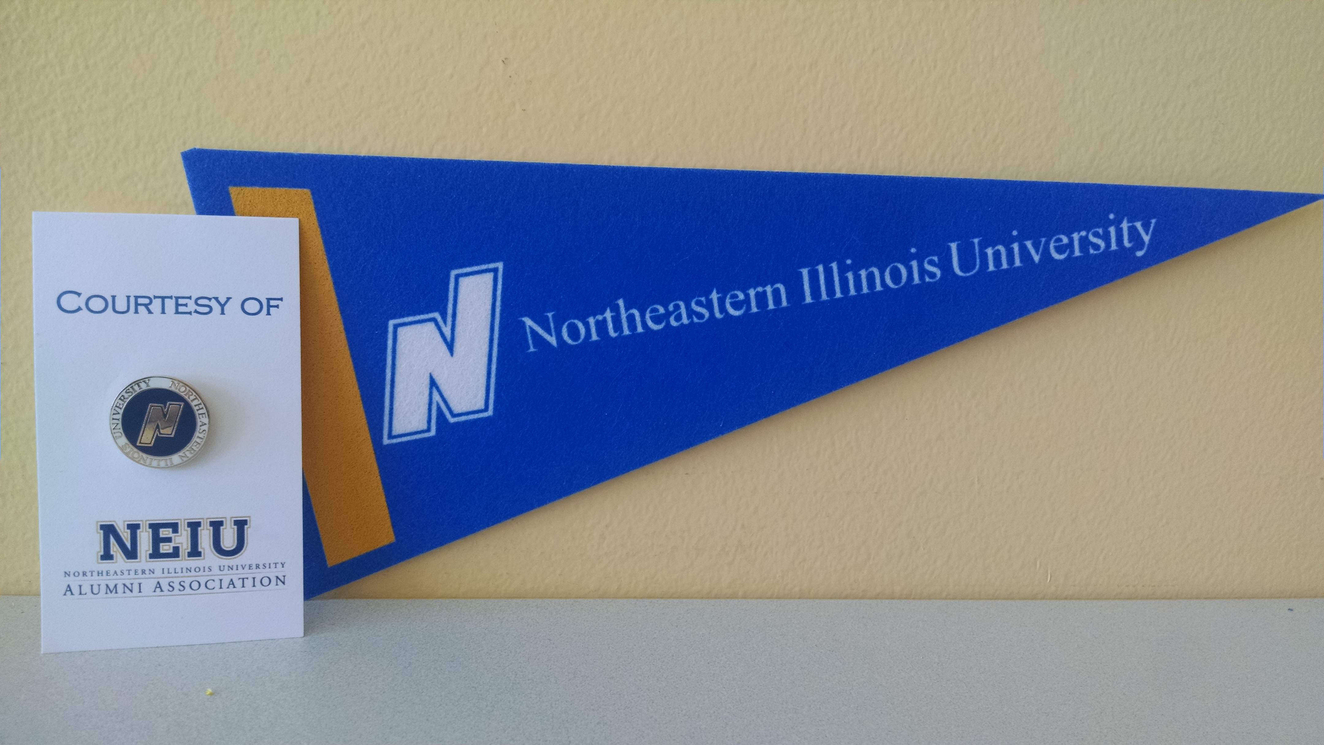 A blue Northeastern pennant hangs on a yellow wall.