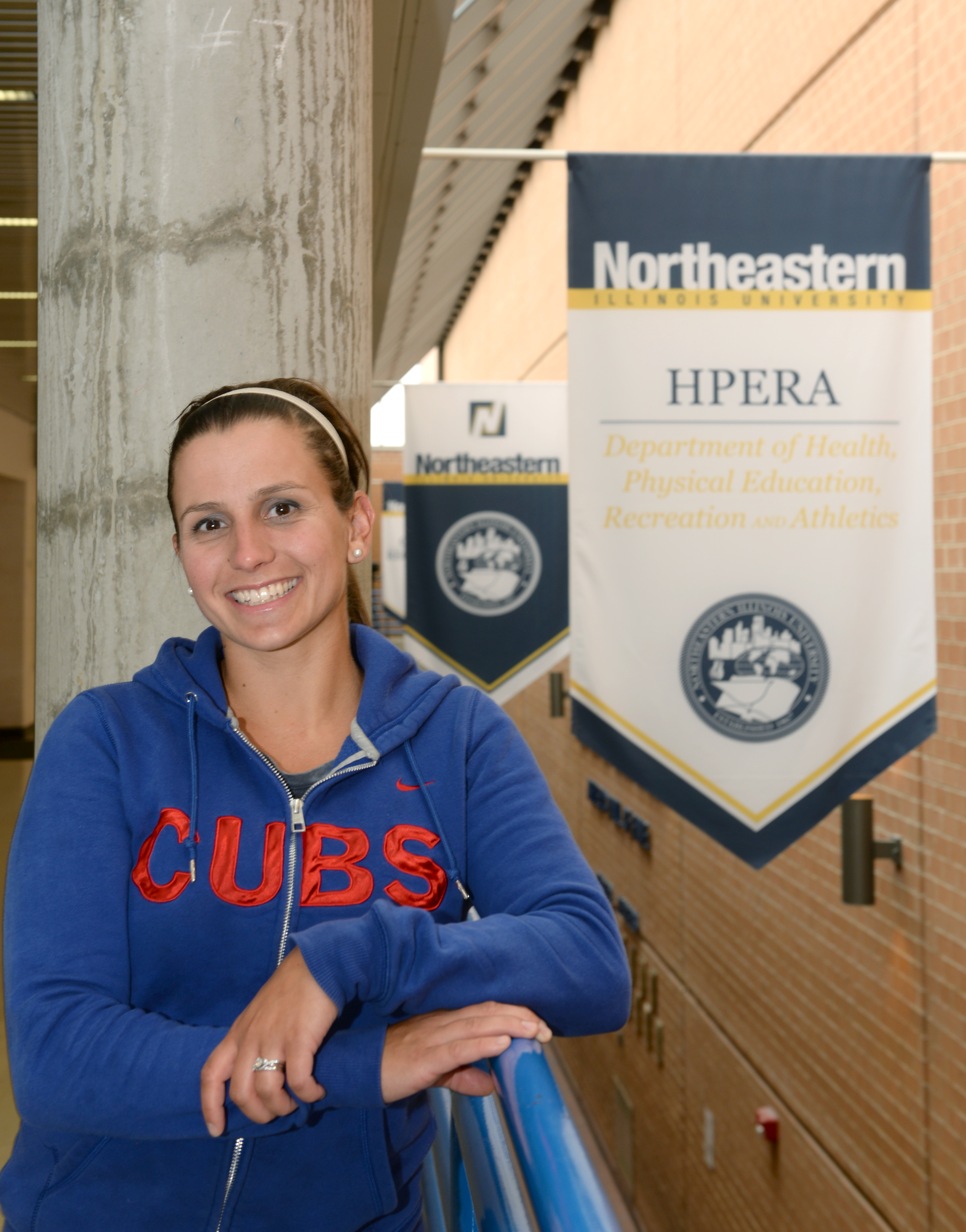 Gina Ridge, Fall 2015 NEIUAA Internship Scholarship recipient, poses in front of two Northeastern signs.