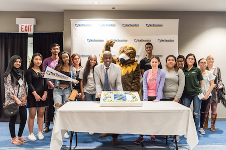 Admissions Director Lamont Vaughn and Goldie pose with a group of newly admitted students
