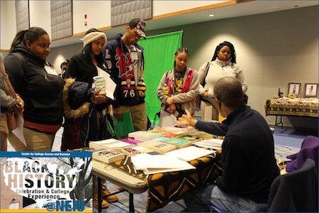 Four CPS students visit a table during the Black History Month Celebration and College Experience.