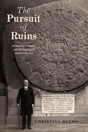 Book cover of The Pursuit of Ruins featuring an ancient carved stone