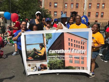 Parade participants hold a CCICS banner during the 4th on 53rd Independence Day Parade in Hyde Park on July 4, 2018.