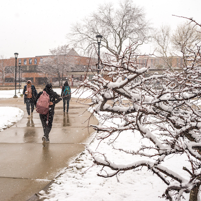 Students walk the paths of the University Commons on a snowy day