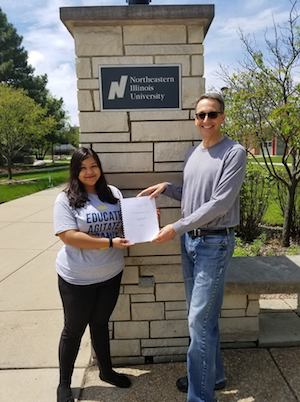 Honors graduate Lizbeth Rosas poses with Anthropology Professor and Honors Program Coordinator Jon Hageman in front of a brick entrance to the Main Campus.