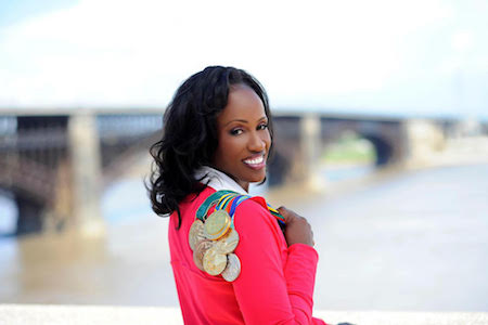 Olympic medalist Jackie Joyner-Kersee looks back over her shoulder, over which are her Olympic medals